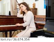 Attractive young woman chooses pianoforte in a record store. Стоковое фото, фотограф Яков Филимонов / Фотобанк Лори
