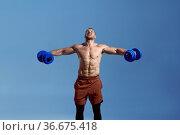 Male muscular athlete with dumbbells in studio. Стоковое фото, фотограф Tryapitsyn Sergiy / Фотобанк Лори
