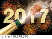 Bottle of champagne with popping cork at new years 2017. Стоковое фото, фотограф Zoonar.com/Wolfilser / easy Fotostock / Фотобанк Лори