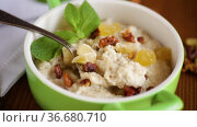 Cooked boiled sweet oatmeal with nuts and candied fruits in a bowl. Стоковое видео, видеограф Peredniankina / Фотобанк Лори