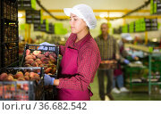 Woman holding crate of peaches during sorting at warehouse, checking quality of fruits. Стоковое фото, фотограф Яков Филимонов / Фотобанк Лори