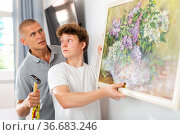Father shows his son how to hang painting on the wall of house. Стоковое фото, фотограф Яков Филимонов / Фотобанк Лори