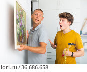 Father and son hang picture together on the wall of house. Стоковое фото, фотограф Яков Филимонов / Фотобанк Лори