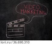 Open movie clapper and speech bubble with video marketing writing... Стоковое фото, фотограф Zoonar.com/Piotr Stryjewski / easy Fotostock / Фотобанк Лори