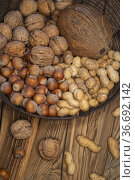 Different kinds of nuts on a wooden background. Стоковое фото, фотограф Richard Semik / easy Fotostock / Фотобанк Лори