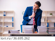 Young businessman employee unhappy with excessive work in the office. Стоковое фото, фотограф Elnur / Фотобанк Лори