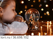 Girl looking at a glass ball with a scene of the birth of Jesus Christ. Стоковое фото, фотограф Ирина Аринина / Фотобанк Лори