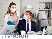 Businessman in face mask working with female assistant in office. Стоковое фото, фотограф Яков Филимонов / Фотобанк Лори