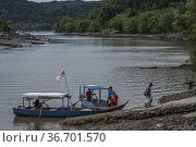 Ferry boat with locals on the Sungai Tabo river, Bako village, Bako... (2017 год). Редакционное фото, фотограф Chua Wee Boo / age Fotostock / Фотобанк Лори