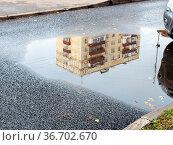 Rain puddle with reflection of municipal urban house on asphalt road... Стоковое фото, фотограф Zoonar.com/Valery Voennyy / easy Fotostock / Фотобанк Лори