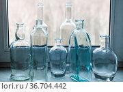 Many empty drunk bottles on windowsill of home window. Стоковое фото, фотограф Zoonar.com/Valery Voennyy / easy Fotostock / Фотобанк Лори