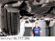 Front car suspension. the garage mechanic raised the car on the lift. Стоковое фото, фотограф Zoonar.com/Konstantin Malkov / easy Fotostock / Фотобанк Лори