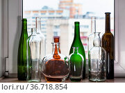 Many empty bottles on windowsill and view of city through home window... Стоковое фото, фотограф Zoonar.com/Valery Voennyy / easy Fotostock / Фотобанк Лори