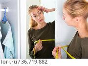 Woman measures breast volume in front of a mirror. Стоковое фото, фотограф Яков Филимонов / Фотобанк Лори
