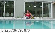 Happy african american plus size woman practicing yoga, using smartphone next to swimming pool. Стоковое видео, агентство Wavebreak Media / Фотобанк Лори
