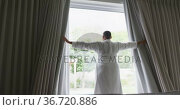 Happy african american plus size woman wearing robe, drawing curtains and looking through window. Стоковое видео, агентство Wavebreak Media / Фотобанк Лори