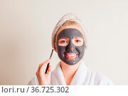 Smiling woman applying black charcoal mask on face at home. Стоковое фото, фотограф Zoonar.com/Oksana Shufrych / easy Fotostock / Фотобанк Лори