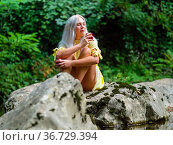 Attractive blonde woman on a Green forest river eating apple looking... Стоковое фото, фотограф Emil Pozar / age Fotostock / Фотобанк Лори
