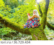 Attractive blonde woman is siting on a tree with a tea-pot in hands... Стоковое фото, фотограф Emil Pozar / age Fotostock / Фотобанк Лори