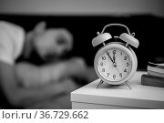White alarm clock on the bedside table. Young man sleeps in the background... Стоковое фото, фотограф Zoonar.com/Patrick Daxenbichler / easy Fotostock / Фотобанк Лори
