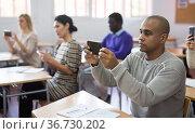 Male student take pictures on smartphone in classroom. Стоковое фото, фотограф Яков Филимонов / Фотобанк Лори