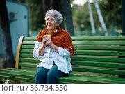 Dranny in scarf drinks hot coffee on the bench. Стоковое фото, фотограф Tryapitsyn Sergiy / Фотобанк Лори
