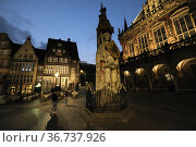 """""""Germany, Bremen - The Roland, a landmark of the Hanseatic city in the evening twilight on the market place, on the right the historical town hall"""" Редакционное фото, агентство Caro Photoagency / Фотобанк Лори"""