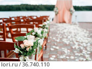 Wedding arch decorated with flowers and wooden chairs on forest lake... Стоковое фото, фотограф Zoonar.com/Konstantin Malkov / easy Fotostock / Фотобанк Лори