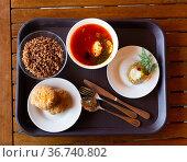 Plates with soup, buckwheat porridge, cutlets and salad on tray. Russian traditional dishes. Стоковое фото, фотограф Яков Филимонов / Фотобанк Лори
