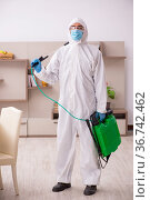 Young male contractor disinfecting at home. Стоковое фото, фотограф Elnur / Фотобанк Лори