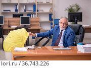 Aged businessman employee looking after newborn at workplace. Стоковое фото, фотограф Elnur / Фотобанк Лори