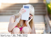 Attractive young woman is talking on a cellular phone and hiding ... Стоковое фото, фотограф Emil Pozar / age Fotostock / Фотобанк Лори