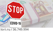 Image of stop covid 19 sign and stacks of euro currency bills. Стоковое фото, агентство Wavebreak Media / Фотобанк Лори