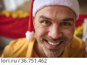 Portrait of caucasian man wearing santa hat smiling at home during christmas. Стоковое фото, агентство Wavebreak Media / Фотобанк Лори