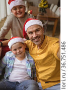 Caucasian father and two sons smiling while talking a selfie at home during christmas. Стоковое фото, агентство Wavebreak Media / Фотобанк Лори