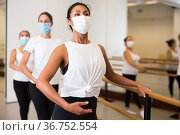 Asian woman in a protective mask stands holding a barre in a ballet stance. Стоковое фото, фотограф Яков Филимонов / Фотобанк Лори