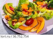 Deliciously salad of baked pumpkin, cherry tomatoes, sesame and sauce. Стоковое фото, фотограф Яков Филимонов / Фотобанк Лори