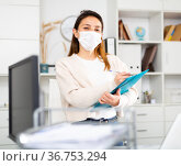 Manager girl stands in a protective mask in the office and fills out documents on a folder. Стоковое фото, фотограф Яков Филимонов / Фотобанк Лори