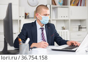 Head of the company in a protective mask writes a business plan on paper, sitting at a laptop. Стоковое фото, фотограф Яков Филимонов / Фотобанк Лори