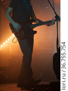 Electric bass guitar player stands on a stage, close-up. Стоковое фото, фотограф EugeneSergeev / Фотобанк Лори