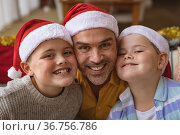 Portrait of caucasian father and two sons wearing santa hat smiling at home during christmas. Стоковое фото, агентство Wavebreak Media / Фотобанк Лори