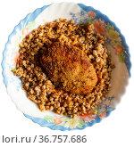 Appetizing buckwheat porridge with cutlet on plate. Healthy food. Russian cuisine. Стоковое фото, фотограф Яков Филимонов / Фотобанк Лори
