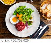 Tartar beef with quail egg and arugula served on plate. Modern French cuisine. Стоковое фото, фотограф Яков Филимонов / Фотобанк Лори