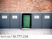 In einer Reihe angeordnete Mülltonnen stehen in verschließbaren Metallboxen... Стоковое фото, фотограф Zoonar.com/Bastian Kienitz / easy Fotostock / Фотобанк Лори