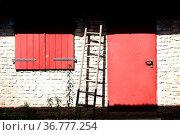 Eine Leiter lehnt im Sonnenlicht an einer Scheune mit einer Holztür... Стоковое фото, фотограф Zoonar.com/Bastian Kienitz / easy Fotostock / Фотобанк Лори