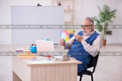 Old male designer working in the office