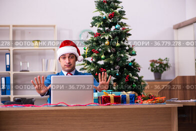Young male employee celebrating Christmas at workplace