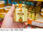 Russia, Yekaterinburg, July 2021: a man's hand holds a jar of honey in the store against the background of shelves .. Text in Russian: only lime honey. Редакционное фото, фотограф Акиньшин Владимир / Фотобанк Лори