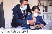 Confident male and female business partners wearing protective masks working in office. New standards due to coronavirus outbreak. Стоковое видео, видеограф Яков Филимонов / Фотобанк Лори