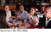 Positive people enjoying pizza and wine in a cozy restaurant. Стоковое видео, видеограф Яков Филимонов / Фотобанк Лори